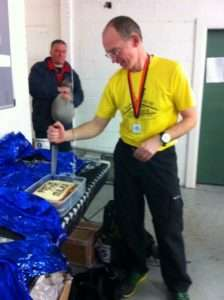 Roy Macdougall watches on as Anthony Corbett cuts the cake marking his entry into the 1000 Miles Club