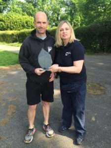 Susan Johnston (Cancer Research) presenting chairman Graham Park with a memento recognising Quakers members support over the years
